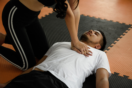 Fitness trainer woman giving cardiopulmonary resuscitation or CPR (life saving techniques) to heart attack drowning shock man in sport club. Urgent accident for Healthcare concept.