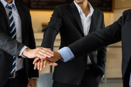 Group of businessman team touching hands together after getting agreement on project.  symbol of teamwork at coffee cafe, ,companionship, unity for Business success.