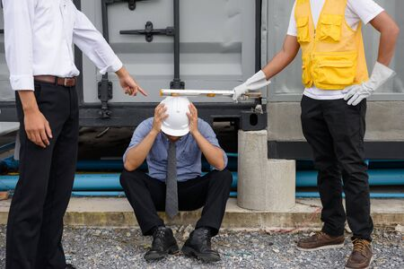 punished: Cheat and Corruption Engineering Asian senior manager is arrested and punished by Foreman and field engineer man at construction site. Sad feeling expression for Business concept. Stock Photo