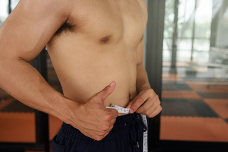 Asian fit and firm man measuring his thin waist of 31 inch by tape measure with thumb up hand sign or ok at fitness sport club. Sport and Healthy lifestyle concept
