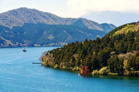 Top view of red torii gate of Hakone shrine and sailing pirate tourist ship on Ashi lake. The pirate ship is one of the most famous Hakone tourist wishlist. Stock Photo