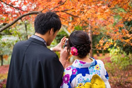 Japanese young couple with Traditional Yukata and Kimono dress using smartphone to selfie with autumn leaf colors during fall season at tenryu-ji temple garden, Arashiyama, Kyoto, Japan.