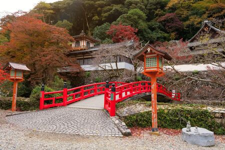 Red bridge with Autumn foliage colors at Minoo Takianji temple in Osaka, Japan. Here, near Minoh waterfall, is famous during fall season.