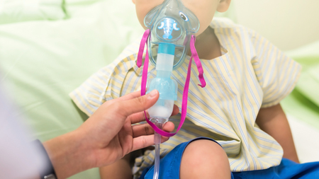 Sick young boy, 3 years old, inhale medication by inhalation mask to cure Respiratory Syncytial Virus (RSV) on hospital bed. Archivio Fotografico