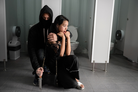 Scary kidnapped woman being threatened by kidnapper holding and strangling her neck by left hand and knife on right hand inside women toilet. Halloween and murderer concept with copy space for text. Stock Photo