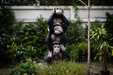 three monkey statues using hand to close ears, eyes, and mouth.  Buddhist religious symbol. Concept and Idea to live in the world.