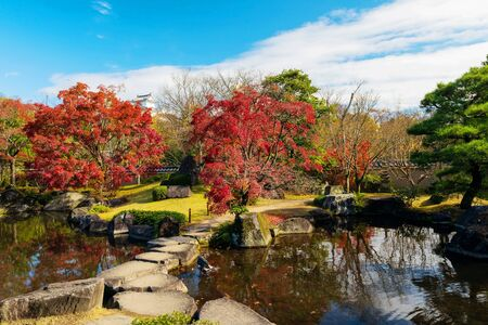 Koko-en autumn garden footpath across the pond with skyline reflection and clear blue sky in Hyogo, Japan. Here is very famous to see fall foliage colors with Himeji castle background. Stock Photo