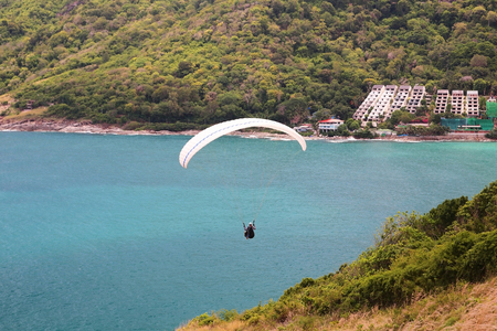 people flying Paramotor near the cliff to enjoy Andaman blue sea at windmill viewpoint in Phuket, Thailand.