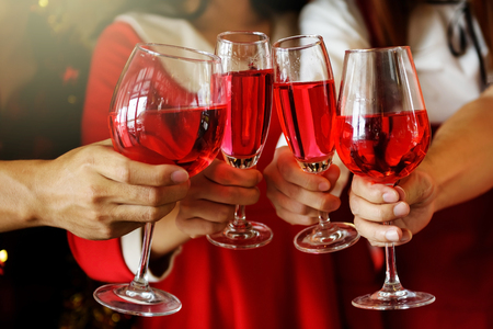 Group of young hands with red wine toasting glasses for Christmas or xmas celebrating party. Closeup photo with bokeh background for ceremony holiday celebration.