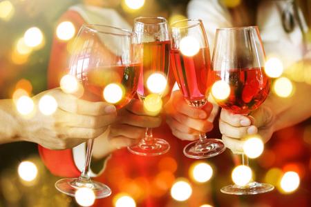 Groep handen die glazen rode wijn roosteren voor Kerstmis of Kerstmis vierende partij. Close-upfoto met bokehlicht voor de viering van de Nieuwjaarsvakantie. Stockfoto