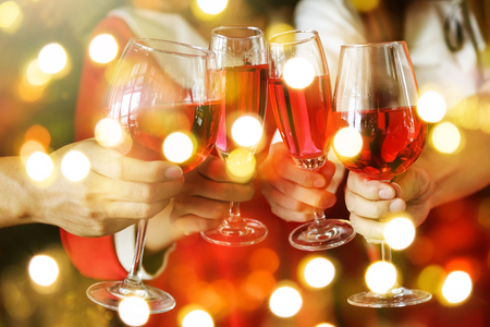 Group of hands toasting glasses of red wine for Christmas or xmas celebrating party. Closeup photo with bokeh light for New year holiday celebration.