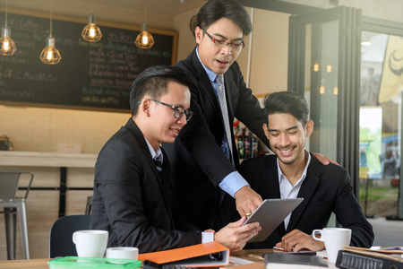 business man boss coaching two happy young businessman by using digital tablet to show project plan and update progress using 4g technology. Fintech business and working from home concept. Archivio Fotografico