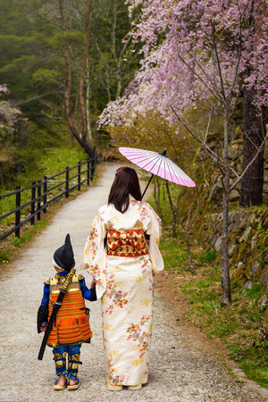 Little samurai boy and Kimono female mother at Saiko Iyashi no Sato Nenba, former farming, village with cherry blossom or sakura near Mt. Fuji, Japan.