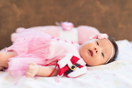 Portrait of adorable smile newborn Asian girl, 1 to 2 months, with pink dress, bow haedband holding red Santa Claus suit. Cute little infant child baby look at camera on soft bed with copy space text