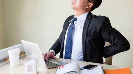 young Asian businessman manager with black suit and neck getting painful feelings and sitting at working table in office while holding his back. Business man trouble of office syndrome. Foto de archivo