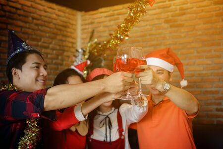Group of Asian happy smile friend hands toasting glasses of red wine for Christmas celebrating party. New year or xmas ceremony for holiday celebration.