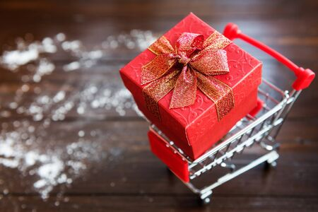 Red Christmas gift box on little shopping cart or Trollye on black dark wooden board background with with snow. Thanksgiving, XMas, and 2018 New year celebration concept. Stock Photo