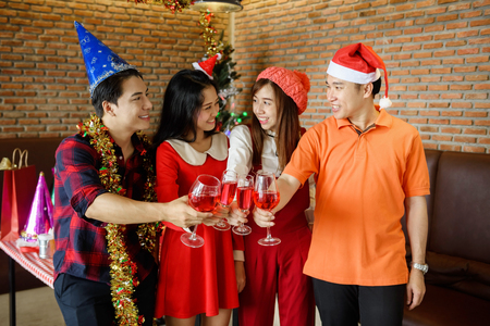 Asian smart friends toasting glasses of red wine or champagne for Christmas celebrating party inside pub and restaurant. Xmas and 2018 New year holiday celebration. Selective focus at glass.