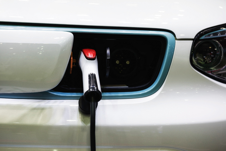 electric car charger plugged into vehicle socket.  charging the battery. New transportation technology to safe the world and environment.  Future without pollution anf gas. Stock Photo