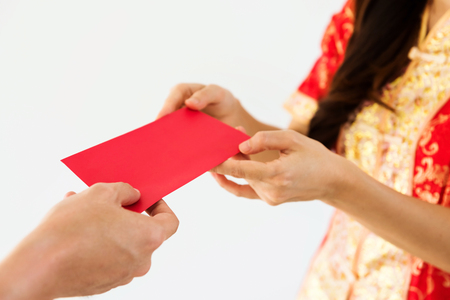 Closeup male hand giving blank red envelopes with money while young woman with Traditional Chinese costume dress, cheongsam, taking a present. Chinese New year holiday celebration on white background. Banque d'images