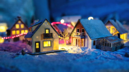 miniature houses in the village with snow at night with light up decoration christmas winter