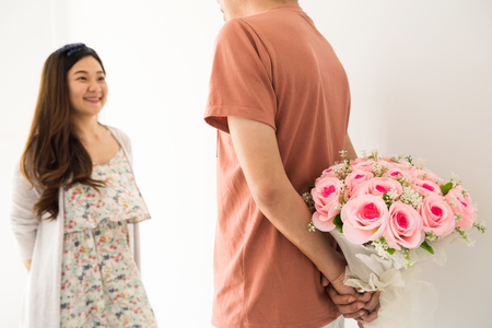 Beautiful happy Asian girl looking at her man while boyfriend holding surprise valentine flower bouquet behind with copy space for text and white background.