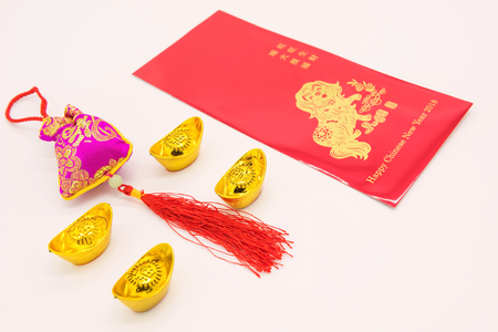 2018 Chinese dog New year red envelope (ang pow), gold ingots, pink sliky money bag isolated on white background with copy space for text. Language on envelop mean Happiness and on ingot mean Wealthy.