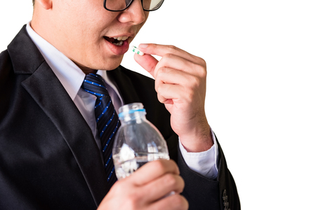 Headache Stress Business man or businessman eating o medical pill and holding bottle of water isolated background on white with copy space for text. Healthy and Medicine concept for office worker.