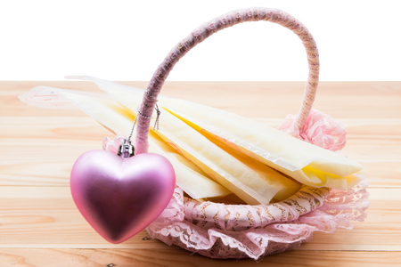 Frozen breast milk in storage bags in basket with pink heart on wood isolated on white background. Nutrition food for baby newborn. WHO (world health organization) recommend to feed at least 6 months.