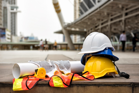Veiligheidshelm hoeden, blauwdruk papier project, meetlint, handschoenen en werknemer jurk op betonnen vloer in moderne stad met wazig mensen. Ingenieur en bouwapparatuur met exemplaarruimte voor tekst.