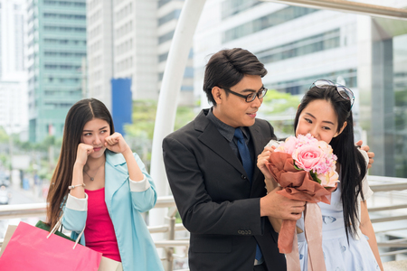Businessman give flower bouquet to cute girlfriend while beautiful girl behind get jealous. Couple in love and a jealous friend watching them in urban city in vValentine day.