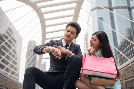 Angry handsome businessman boyfriend look at watch to blaim his girlfriend to miss appointment time due to shopping. girl feel sorry with many merchant bags with city background.