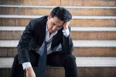 Portrait de stress désespéré senior homme d'affaires assis sur l'escalier avec un sentiment triste après ne pas obtenir de bonus et de promotion. KPI non atteint et projet d?entreprise non réussi.