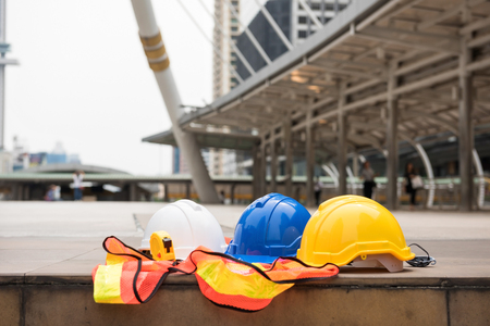 Safety white, blue, yellow helmet hats, measure tape, and worker dress on concrete floor at modern city with blurred people. Engineer and construction equipment with copy space for text. Stock Photo