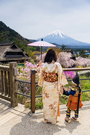 Samurai son boy and Japanese Kimono mother at Saiko Iyashi no Sato Nenba, former farming, village with cherry blossom or sakura and moutain Fuji background, Yamanashi, Japan.
