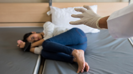 criminalof Sadism hand with white glove attack victim hostage girl on bed being tie hands by belt. Role play game of couple having sex in the bedroom or Social issue of woman rape safety. Stock Photo