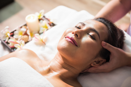 Asian beautiful tan woman in spa salon. Body care treatment by Thai oil. Cute girl massage at head by massage therapist hands with candle and Plumeria on bed with copy space for text.