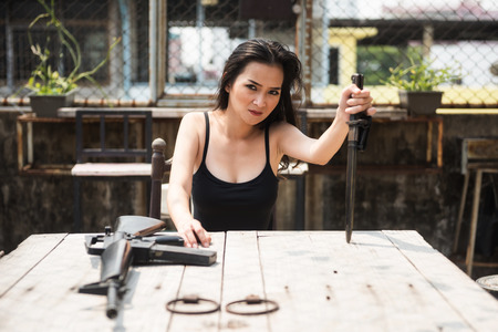 Portrait of dangerous gangster sexy woman holding a knife with M16 gun weapon on table. Mafia, Abuse, Crime, and drug illegal concept against law. Stock Photo
