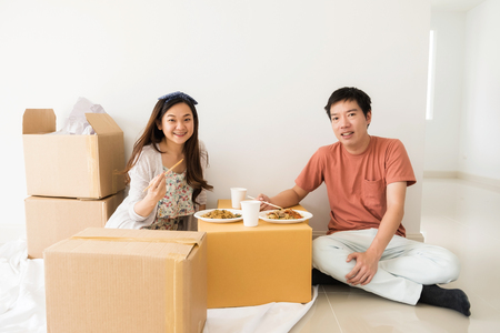 Portrait of Asian couple sitting on floor and eating roasted duck egg noodle on cardboard moving boxes at new house. Architecture and Real estate industry to start new family life.