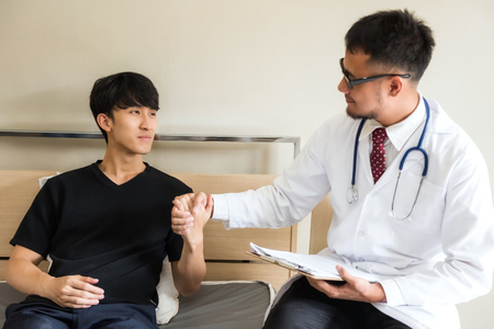 Asian doctor handshake with happy Korean patient man to cheer up after recovering from stomachache sickness on hospital bed. Health care and insurance industry concept. Banco de Imagens
