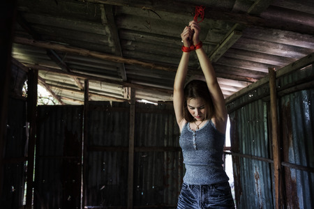 Depress beautiful Asian girl tied hands with red rope on dirty roof ceiling in abandoned house. Hostage concept or female kidnapped from robber. Sexual abuse, rape, Crimical, Victim.