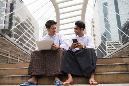 Handsome happy Burmese or Myanmar businessmen with longyi traditional dress working in Modern city. Fintech Foreign Business partner listen good news from smartphone. teamwork and smile coworker.