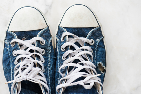 Pair of old worn out blue sneaker by top view. Teenager fashion and lifestyle concept. Used Footwear or shoes for sale in market. Stok Fotoğraf