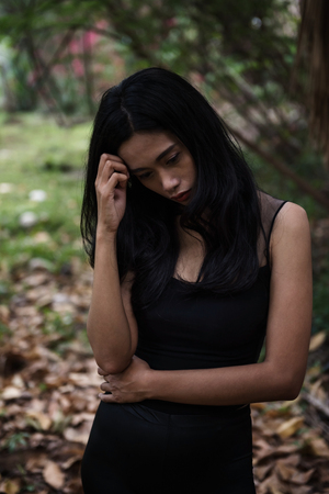 Stress Asian woman with sad feeling stand in the forest. Social issue of mental, health, depress, headache, or addiction concept. Banque d'images