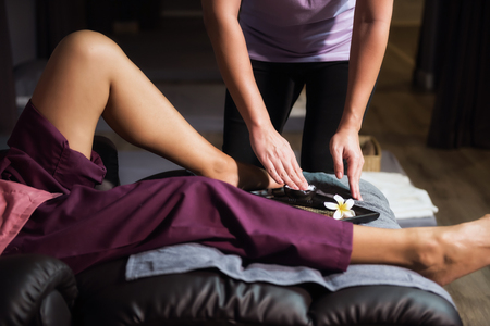 Profesional female massager hand grab aroma lotion or cream to apply to Foot, calf, and legs on sofa. Thai massage treatment in spa salon. Healthy lifestyle concept.