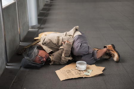 Old sick beggar or Homeless dirty man sleeping on footpath with guitar, donate bowl, paper cardboard with help text. feeling cold during winter with bad weather. Stock Photo