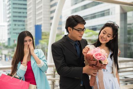 El hombre de negocios le da un ramo de flores a la linda novia china mientras la hermosa niña se pone celosa. Pareja de enamorados y compadecido amigo mirándolos en la ciudad urbana en el día de San Valentín.