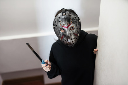 Female model with Jason mask and black dress costume hold knife on hand. Scary human for 2018 Halloween concept with copy space for text. Standard-Bild