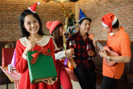 Asian happy girl with Santa hat get surprise xmas gift from boyfriend while others cerebrate by drinking red champagne and playing ukulele. Christmas party concept with copy space for text.