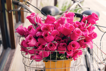 Pink fake flowers on front basket of vintage bicycle. Antiquw color tone.